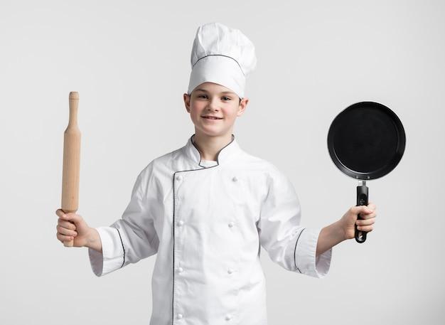 Вид спереди молодой мальчик, одетый как шеф-повар, держа инструменты