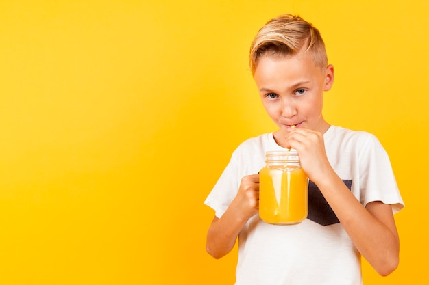 Front view young boy drinking orange fresh