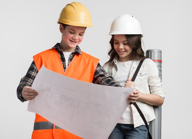 Front view young boy and girl reading construction plan