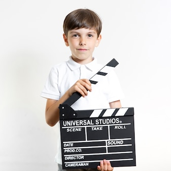 Front view young boy holding clapperboard