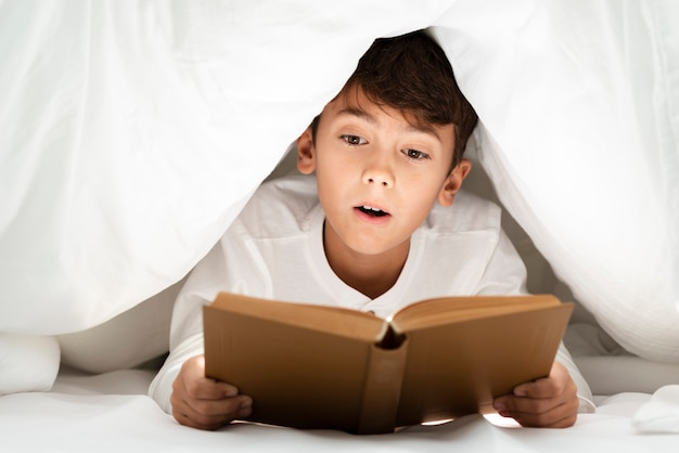 Front view young boy at home reading