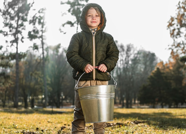 Front view of young boy outdoors holding bucket