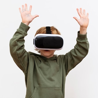 Vista frontale del giovane ragazzo utilizzando le cuffie da realtà virtuale