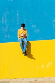 Front view of a young boy wearing casual clothes sitting on a yellow fence against a blue wall while using a smartphone