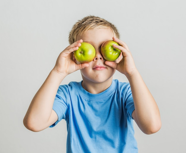 Front view young boy with apples