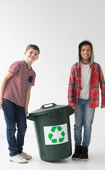 Front view young boys holding recycle bin