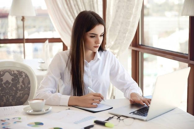 Front view of a young brunette businesswoman which is working on the laptop and writing something down