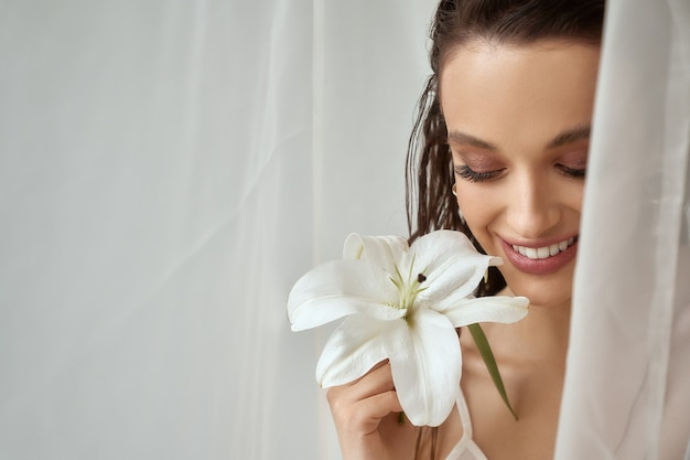 Front view of young brunette woman with perfect makeup and clean fresh skin holding lily flower. portrait of smiling girl with wet hair posing on white background between tulle. concept of beauty.