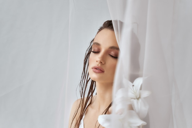 Front view of young brunette woman with perfect makeup, clean skin and closed eyes holding lily flower. portrait of girl with wet hair posing on white background between tulle. concept of beauty.