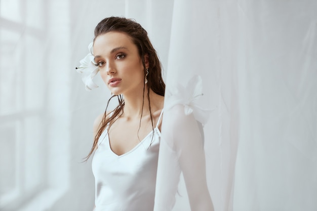 Front view of young brunette woman with perfect makeup and strong face holding lily flower behind ear. portrait of girl with wet hair posing on white background between tulle. concept of beauty.