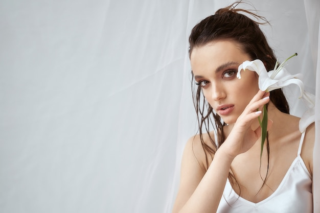 Front view of young brunette woman with perfect makeup and strong face holding white lily flower. portrait of girl with wet hair posing on white background between tulle in morning. concept of beauty.