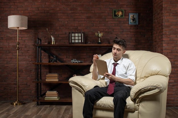 Front view of young businessman sitting on sofa reading from copybook inside room worker work job office