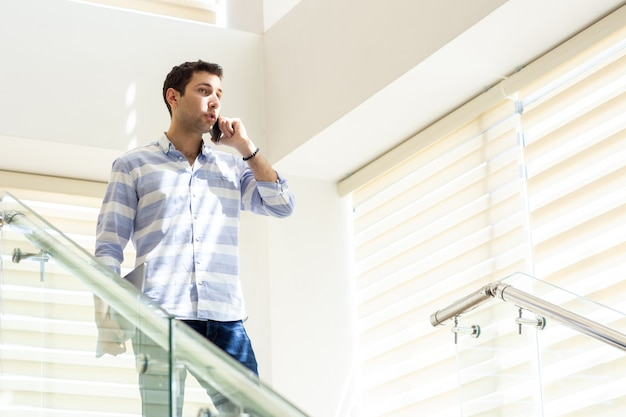 A front view young businessman in striped shirt talking and discussing work issues on the phone during daytime work activity building