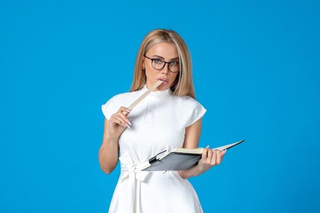 파란색에 메모장이 있는 아름다운 흰색 드레스를 입은 전면 보기 젊은 사업가