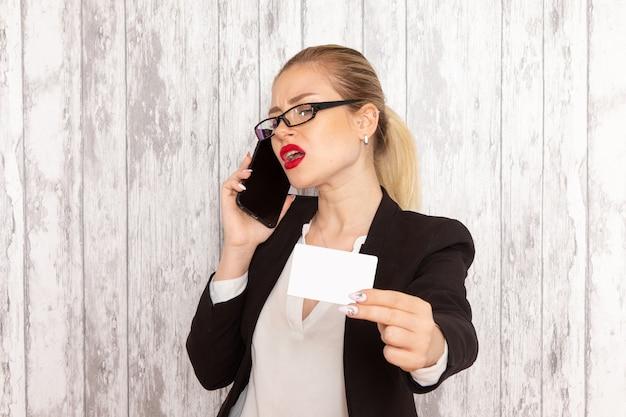 厳格な服を着た若い実業家の正面図明るい白い表面にカードと電話を保持している黒いジャケット