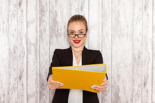 Вид спереди молодой деловой женщины в строгой одежде, черной куртке, держащей файлы и документы на светлом белом столе
