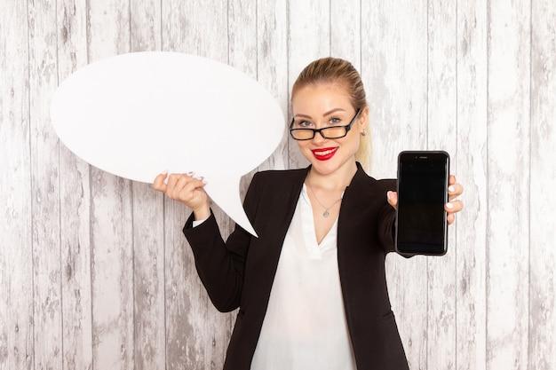 Вид спереди молодой бизнес-леди в строгой одежде, черной куртке, держа свой телефон и белый знак на белой поверхности
