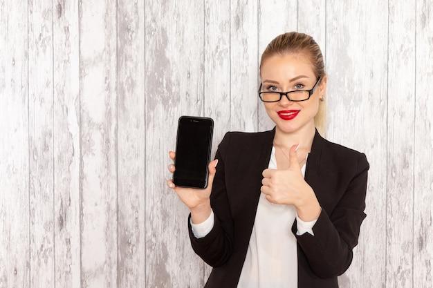 白い表面に彼女の電話を保持している厳格な服の黒いジャケットの正面図若い実業家