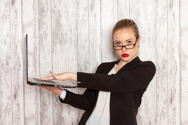 밝은 흰색 책상에 그녀의 노트북을 사용하는 엄격한 옷 검은 재킷에 전면보기 젊은 사업가