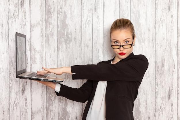 Вид спереди молодой предприниматель в строгой одежде черной куртке, используя свой ноутбук на белой поверхности