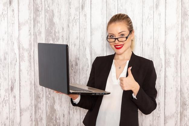 흰색 책상에 웃는 그녀의 노트북을 사용하는 엄격한 옷 검은 재킷에 전면보기 젊은 사업가
