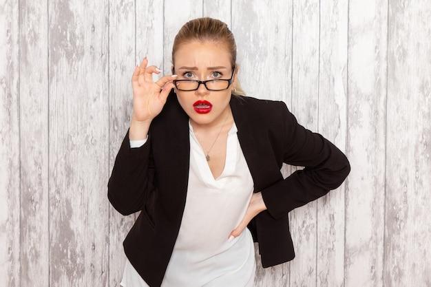 Вид спереди молодой бизнес-леди в строгой одежде, черной куртке с оптическими очками, позирует на белой стене, работа, офис, бизнес