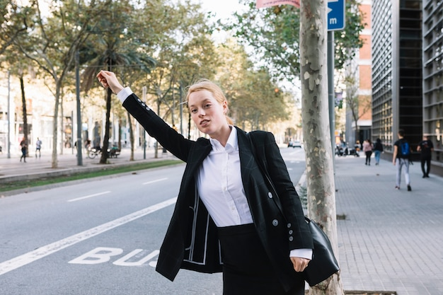 Front view of young businesswoman standing on the road hailing a cab taxi