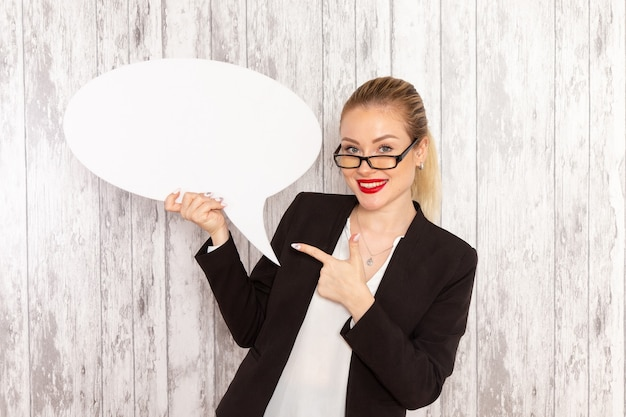 Front view young businesswoman in strict clothes black jacket holding big white sign on light-white surface