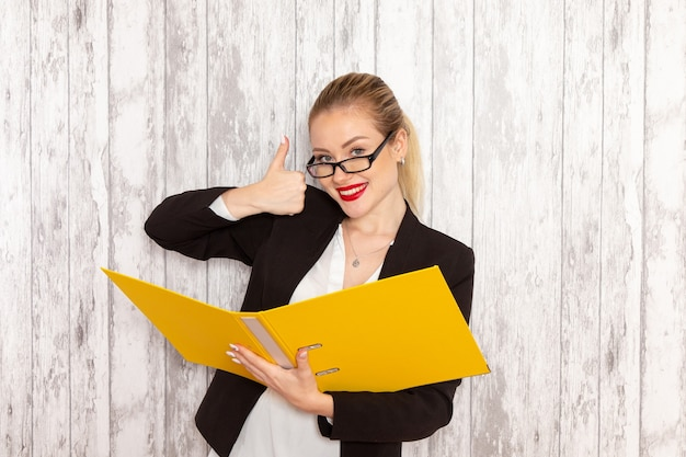 Front view young businesswoman in strict clothes black jacket holding files and documents on light-white surface