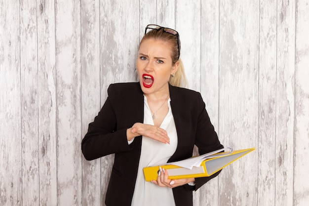 Front view young businesswoman in strict clothes black jacket holding files and documents on white desk