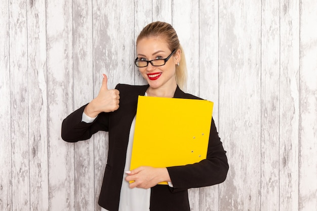 Front view young businesswoman in strict clothes black jacket holding files and documents on the white surface