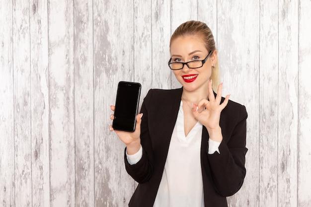 Giovane donna di affari di vista frontale in rivestimento rigoroso del nero dei vestiti che tiene il suo telefono con il sorriso sulla superficie bianca