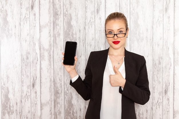 Front view young businesswoman in strict clothes black jacket holding her smartphone on white surface