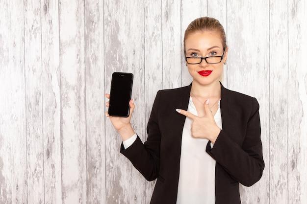 Giovane donna di affari di vista frontale in giacca nera vestiti rigorosi che tiene il suo smartphone sulla superficie bianca