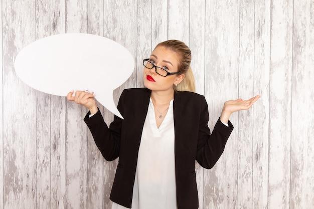 Giovane donna di affari di vista frontale in rivestimento rigoroso del nero dei vestiti che tiene il segno bianco enorme sulla superficie bianca