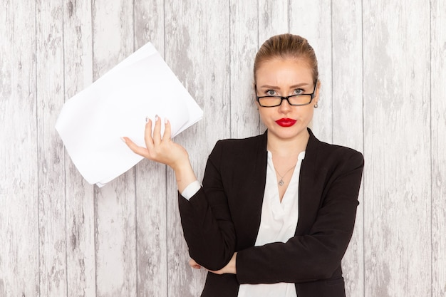 Front view young businesswoman in strict clothes black jacket reading document on white desk