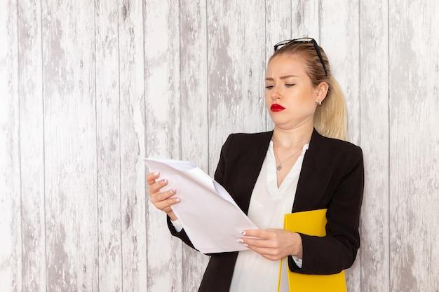 Vista frontale giovane imprenditrice in abiti rigorosi giacca nera leggendo il documento su superficie bianca