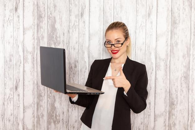 Vista frontale giovane imprenditrice in abiti rigorosi giacca nera utilizzando il suo computer portatile sullo scrittorio bianco chiaro