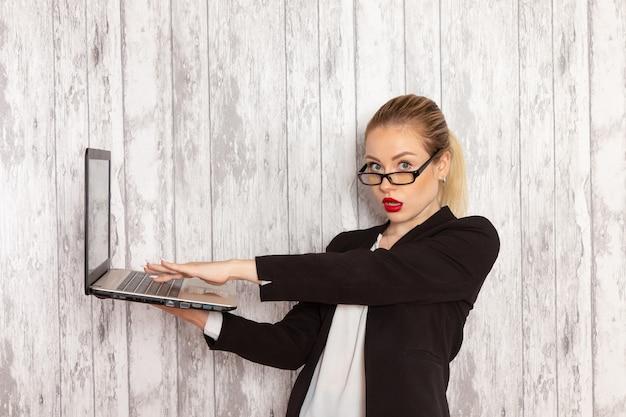 Vista frontale giovane imprenditrice in abiti rigorosi giacca nera utilizzando il suo computer portatile su superficie bianca
