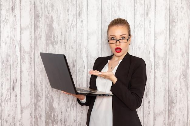 Vista frontale giovane imprenditrice in abiti rigorosi giacca nera utilizzando laptop su scrivania bianca lavoro lavoro ufficio affari