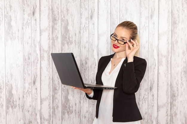 Front view young businesswoman in strict clothes black jacket using laptop on white desk work job office business
