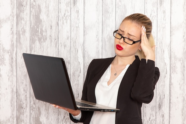 Front view young businesswoman in strict clothes black jacket using laptop on the white wall work job office business worker female
