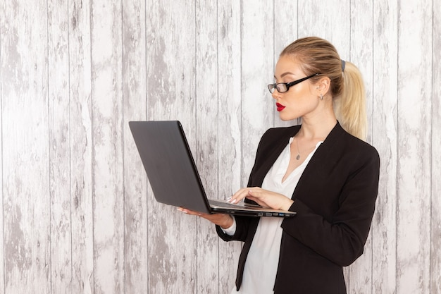 Front view young businesswoman in strict clothes black jacket using laptop on white wall work job office business