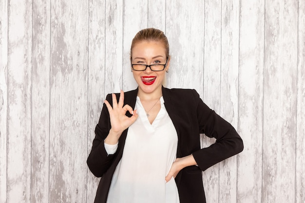 Front view young businesswoman in strict clothes black jacket with optical sunglasses posing on grey white wall work job office business woman lady