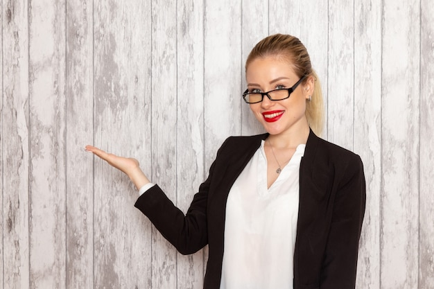 Front view young businesswoman in strict clothes black jacket with optical sunglasses posing and smiling on white wall work job office female business