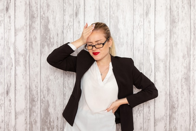 Front view young businesswoman in strict clothes black jacket with optical sunglasses posing on the white desk work job office business woman lady