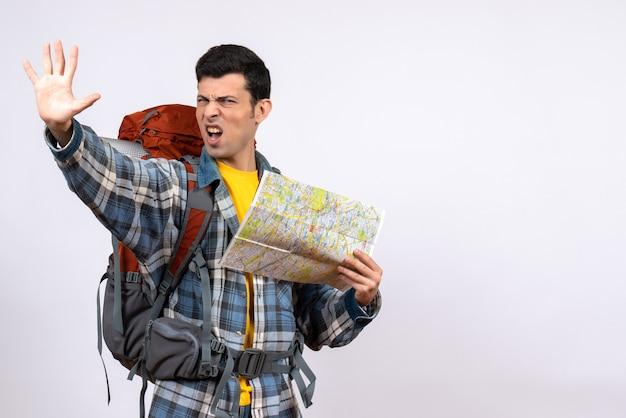 Вид спереди молодой турист с рюкзаком, держащим карту, делая знак остановки