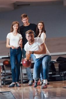 Vista frontale. i giovani amici allegri si divertono al bowling durante i fine settimana