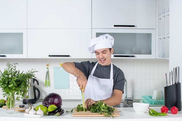 부엌에서 커팅 보드에 균일한 절단 채소를 입은 전면 보기 젊은 요리사