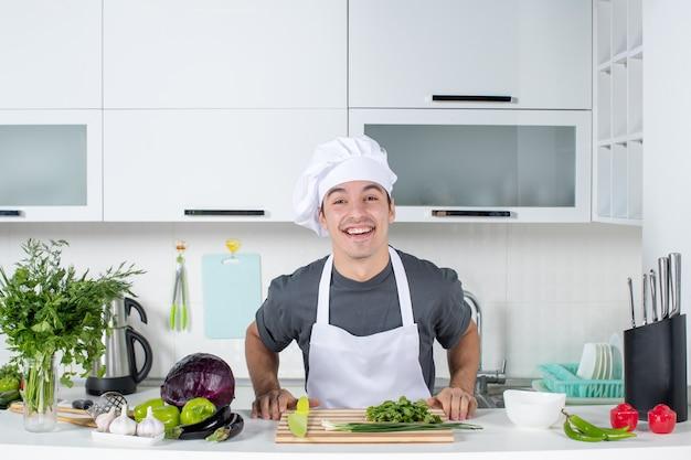 Вид спереди молодой шеф-повар в униформе смеется